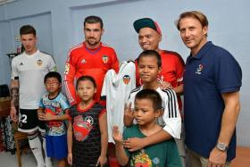STARS PAY VISIT: Valencia striker Santi Mina (left), goalkeeper Mathew Ryan (second from left) and former midfielder Gaizka Mendieta (right) visit a family at their home at Beo Crescent.