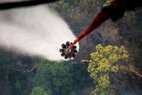 WATERWORKS: The Chinook is flown to a water source and a heli-bucket - which can hold up to 5,000 litres of water - is lowered to collect water for dousing flames at a hotspot.