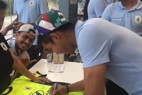 STAR POWER: Stags' goalkeeper Izwan Mahbud putting his autograph on a jersey at the launch of the Pentagon Football Academy.