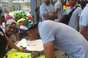 OFF-FIELD INITIATIVES: Stags' goalkeeper Izwan Mahbud autographing a jersey at the club's launch of the Pentagon Football Academy at the Decathlon store in Bedok, as teammate Jermaine Pennant (wearing red cap) looks on.