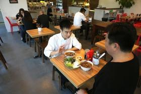 THE 'POTUS EFFECT': (Above) Chef Le Van Tuan of local restaurant Uncle Ho Tuckshop explaining to our reporter what goes into bun cha.