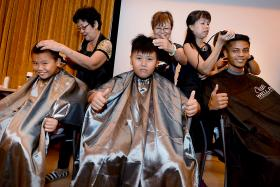 NOBLE CAUSE: (From left) Brothers Alex Chong Kwok Ching and Christopher Chong Kwok Hui, aged 10 and 12, with Abdul Thaslim, 18, at StarHub's Hair For Hope event.