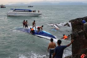 OVERTURNED: Rescue workers search for victims after the crash. One British man is still missing.