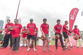 BOUNCE AWAY: Minister for Social and Family Development Tan Chuan-Jin (fourth from far left in front row) and Ministry for Culture, Community and Youth Parliamentary Secretary Baey Yam Keng (fifth from far left) leading the Singapore Book of Records attempt for the most number of people bouncing basketballs together. A total of 2,180 participants combined to break the record.