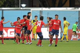JOY: The Young Lions (in red) celebrating their late equaliser against Ceres 