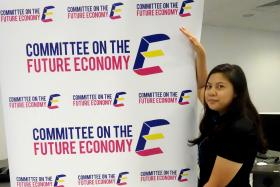 EYE-CATCHING: Miss Nur Hazirah Su'Aidi with her winning logo, which is designed to look like a staircase.