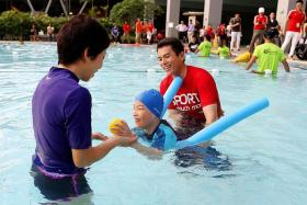 BUILDING TOWARDS AN ALL-INLCUSIVE SOCIETY: Minister for Culture, Community and Youth Grace Fu (in purple) interacting with Teo Choon Khang (centre), who has cerebral palsy, and swim coach Danny Ong at the ActiveSG Sengkang Sports Centre, which is the first Centre of Expertise for Disability Sports.