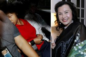 Indonesian maid Dewi Sukowati, wearing a red polo T-shirt, in a police car on 20 March 2014. She was charged with the murder of socialite and philanthropist Nancy Gan Wan Geok.