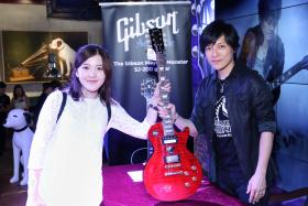 FAN: Monster with superfan Cynthia Zhu, who flew from New York City to Hong Kong to have her Epiphone Mayday Monster Les Paul electric guitar signed by the guitarist himself.