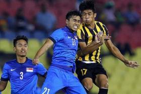 CHALLENGE: Singapore U-21 captain Ammirul Emmran (No. 21) goes up for a header with Malaysia U-21 forward Muhammad Syafiq Ahmad.
