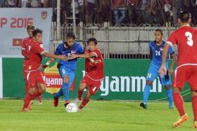 IT TAKES TWO: (Above) Singapore left back Hafiz Abu Sujad (in blue) charging his way past Myanmar's Ye Ko Oo (far left) and David Htan as Zulfadli Zainal Abidin (No. 24) looks on.