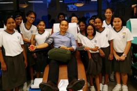 AWARDED: Mr Koh Wee Jin Algene donating blood while primary school pupils look on.