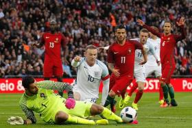 NO SMALL MATTER: Chris Smalling ensuring England go into Euro 2016 on a winning note after scoring the only winner in the friendly against Portugal. FOILED: Portugal goalkeeper Rui Patricio saving an attempt by Wayne Rooney (No. 10).