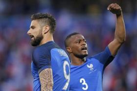 TEAM SUPPORT: Patrice Evra (above, right) urging French fans to cheer his teammmate Olivier Giroud (above) during their final warm-up game against Scotland.