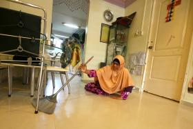 RESILIENT: Madam Fatimah Bivee, 53, crawling in her flat to sweep it every day.