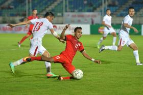 DOWNED: Faris Ramli (in red) struggling against the Vietnam players.