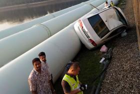 MANGLED: It took five other motorists to free the Singaporean driver who was reportedly trapped in his wrecked car after crashing onto the railway tracks along the Causeway and landing on the water pipes (above).