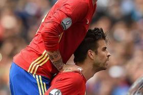 SPANISH DELIGHT: Sergio Ramos (above) celebrating with goal scorer Gerard Pique as Spain get their winning start to Euro 2016 despite the heroics of Czech goalkeeper Petr Cech.