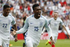 Daniel Sturridge celebrates after scoring England's late winner against Wales.
