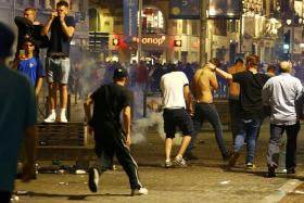 HOOLIGANS: England fans (above) running away from tear gas, as riot police look to disperse rowdy fans in central Lille on Wednesday.