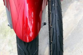 SIDE-BY-SIDE COMPARISON: A standard front tyre (on the motorcycle) compared to an uninflated skinny tyre called sotong.