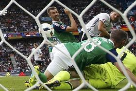 ONE UP: Mario Gomez (top right) putting the ball past Northern Ireland goalkeeper Michael McGovern for Germany's only goal.