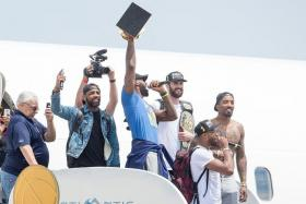 HOMECOMING: LeBron James (in colour) and his Cavaliers teammates return to Cleveland with the NBA trophy in tow.