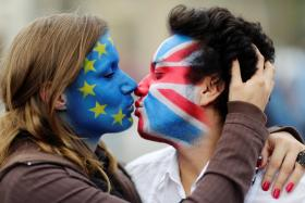 KISS & MAKE UP? Two activists with the EU flag and Union Jack painted on their faces kiss each other, symbolising a preference for the UK to stay in the EU.