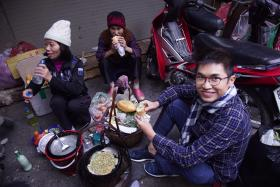 BLENDING IN: Jason Yeoh having a sidewalk meal with locals in Vietnam.