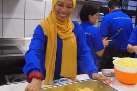 HAPPY: Ms Juzailah Abdul Rahin cooking for the needy.