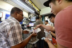 SELLING FAST: Money changers at The Arcade in Raffles Place doing a brisk trade yesterday.