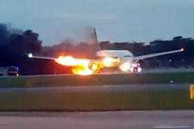 ABLAZE: (Above) The right wing of the plane caught fire after landing.