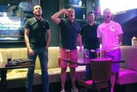 HIGH BEFORE THE LOW: England fans singing their national anthem with gusto at McGettigan's in Clarke Quay yesterday morning before the team's shambolic 2-1 loss to Iceland.