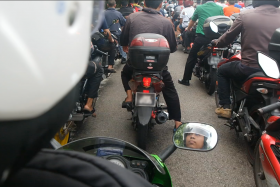 Ngee Ann Polytechnics student Muhammad Fareez Buhari (reflected in the motorcycle mirror) has to endure the long wait on the causeway to travel back to his home in Johor Baru to break fast.