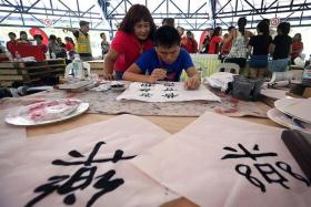FOCUSED: (Above) Leow Wei En, 18, was introduced to calligraphy just seven months ago. At the Rock Our Blocks party, he demonstrated his skill with confidence. His mother Jocelyn Toh, 52, watches as he practised his craft.