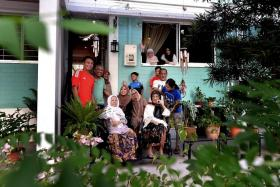 CLOSE: (Above) The four families break fast at Madam Rozana's (in glasses at window) home almost every day.