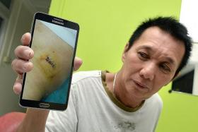 ARGUMENT: The incident happened at a coffee shop at Block 475, Choa Chu Kang Avenue 3. CELEBRATION TURNED SOUR: Mr Yue Tuck Choy, 59, showing the stab wound.