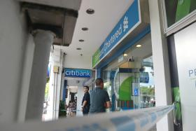 CLOSED: Police cordoned off the area in front of Standard Chartered bank at Holland Avenue after a rare robbery.