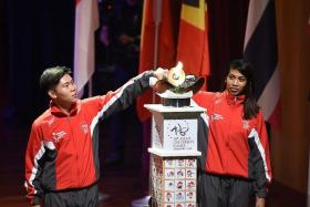 KICKING THINGS OFF: Singapore archer Ang Han Teng (left) and silat exponent Nur Shafiqa (right) lighting the cauldron to mark the start of the 18th Asean University Games.