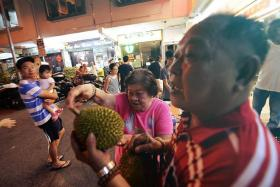 WORTH IT: Retiree Ng Mui Yong (centre) queued under the sun to be first in line to receive free durians from seller Yap Kean Seng.