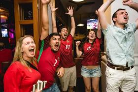 FINALLY: Portugal fans celebrating their team's first major triumph at the McGettigan's bar at Clarke Quay yesterday morning.