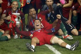 FROM TEARS TO CHEERS: Ronaldo celebrates with teammates and trophy.