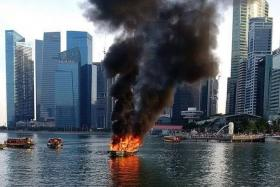 SMOKE: Plumes of black smoke could be seen around Marina Bay as fire blazed through the bumboat.