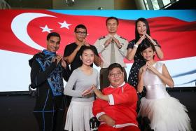 TOGETHER: (Back row, from left) SAF Music and Drama Company aerialist Rajid Ahamed, actor Rizman Putra Ahman Ali, show chairman Senior Lieutenant-Colonel Jason See and creative director Beatrice Chia-Richmond. (Front row, from left) Singapore Soka Association performer Tay Qing Yi, Handicaps Welfare Association performer Quek Swee Hai and sign language instructor Neoh Yew Kim. They are demonstrating the sign language for the word 'home'.