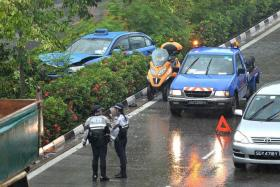 DAMAGED: A blue Comfort taxi landed in the central divider after a multiple-vehicle collision at West Coast Highway towards Jalan Buroh.