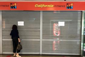 A member peering through the shutters of the now-closed California Fitness' Novena Square outlet on the afternoon of July 20.