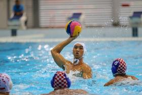 MAIDEN SUCCESS: NUS' Ang An Jun helping Singapore narrowly beat Indonesia in the men's water polo final at the 18th Asean University Games yesterday. This is the first time the sport is featuring in the Games.