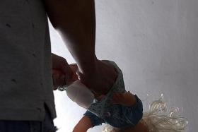 ABUSE: The man dangled his baby daughter upside down by one leg.
