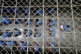 LIFE IN KLONG PREM: (Above) Inmates sitting in rows during an inspection visit; a cell with a toilet where five inmates sleep; visitors speaking by phone to inmates.