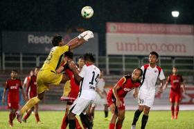 OUCH: Balestier goalkeeper Naqiuddin Nodin (in yellow) colliding with teammate Fadli Kamis while punching away a corner kick. TNP